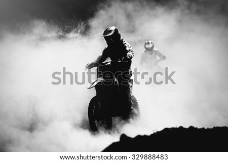 Motocross racer accelerating in dust track, Black and white, high contrast photo - stock photo