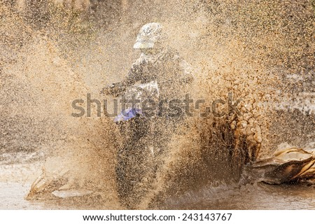 Motocross racer in a wet and muddy terrain in Parola, Finland. Water and mud splashing everywhere and covering the driver completely. - stock photo