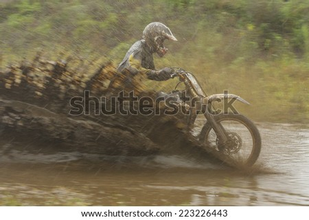 Motocross racer on wet and muddy terrain - stock photo