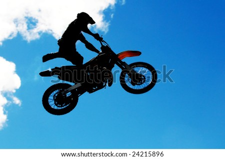 Motocross rider doing some daring tricks in a high jump - stock photo