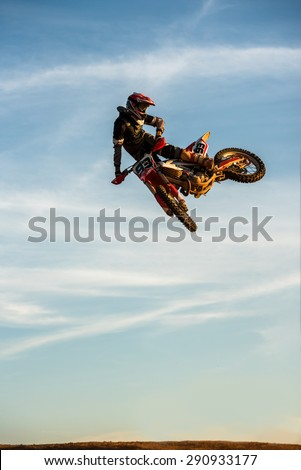 Motocross Rider Jump in a blue sky with clouds - stock photo