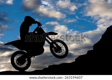 Motocross - silhouette with a rock and blue sky - stock photo