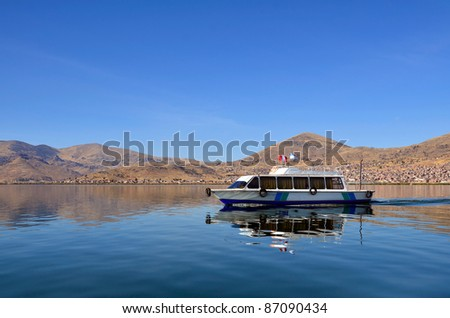 Motor Boat on Calm Lake Titicaca with Puno City in the Background - stock photo