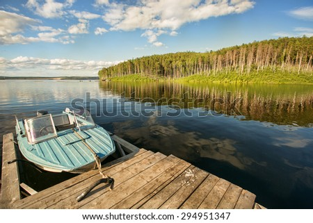 Motor Boat on the Lake near the pine forest - stock photo