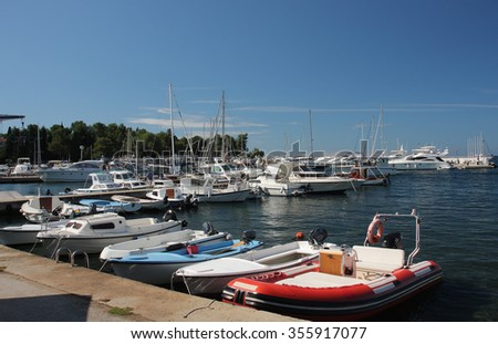 Motor boats and sailboats in harbor in Porec,Croatia  on a summer day - stock photo