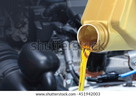 Motor oil pouring, Pouring oil lubricant motor car from bottle - stock photo