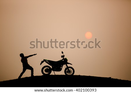 motorbike and biker with sunset background - stock photo