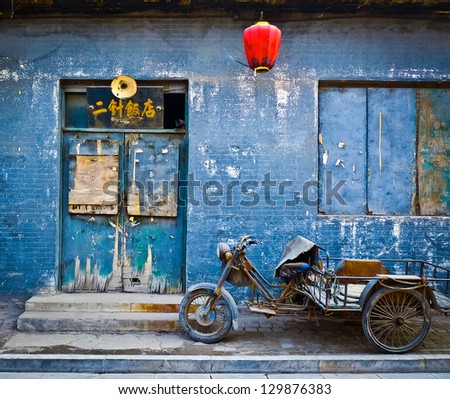 Motorbike cart parked in front of the decaying blue facade of an abandoned shop in Pingyao, China - stock photo