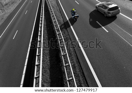 motorbike overtaking a car on a highway seen from above - stock photo