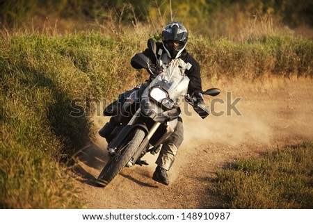 Motorbike rider on track. Strong grain added to create atmosphere, outdoor shot. - stock photo