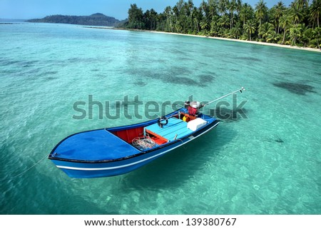 Motorboat in front of beautiful seascape with tropical beach and turquoise water  - stock photo