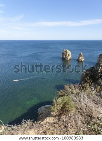 Motorboat with people relaxing in the sun at lagos bay, near Ponta da Piedade, Algarve, Portugal - stock photo