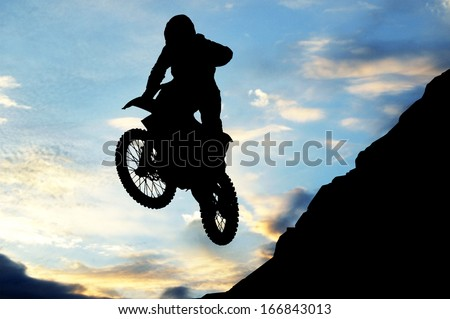 motorcycle jumping from a high rock - stock photo