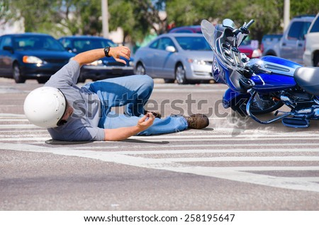 Motorcycle rider has wrecked and is laying in the road as his motorcycle goes sliding into the busy intersection.  - stock photo