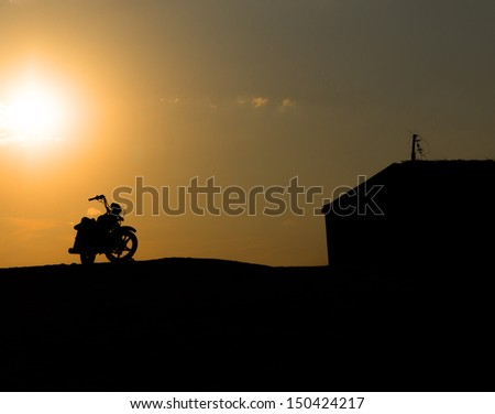 Motorcycle silhouette against the sunset - stock photo