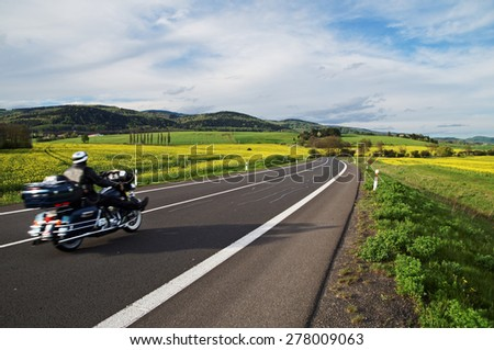 Motorcycle traveling along an empty asphalt road between yellow blooming rape fields in the rural landscape. In the background of forested mountains. - stock photo