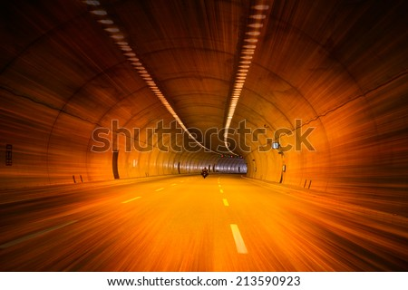 Motorcyclist driving through highway road tunnel  - stock photo