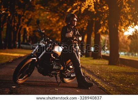 Motorcyclist with a cafe-racer motorcycle outdoors - stock photo