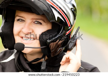 Motorcyclist with hands-free phone system - stock photo