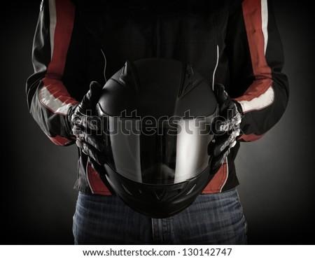 Motorcyclist with helmet in his hands.  Dark background - stock photo