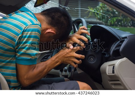 Motorists are sitting bent and flexed arm to hold the steering wheel because of a drunk. - stock photo