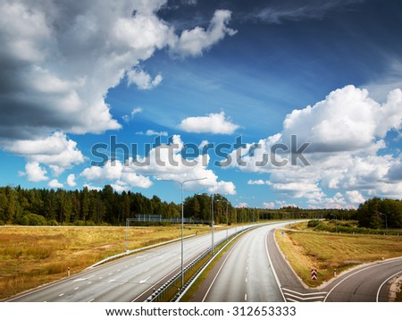 Motorway in summer with beautiful white clouds - stock photo