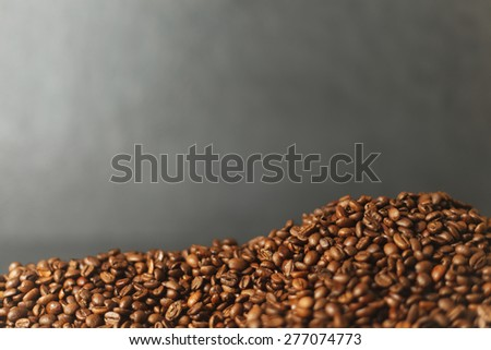 Mound of Coffee beans on stone surface  - stock photo