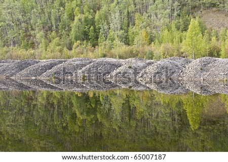 Mounds of gravel from a gold dredge are reflected in a tailings pond - stock photo