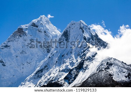 Mount Ama Dablam in Himalaya Mountains, Nepal. Beautiful landscape, summits in bright high mountains over blue sky. - stock photo