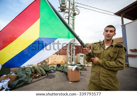 Mount Carmel, Israel - October 28, 2015: Israeli soldier with Druze flag. Group of them was installing Israeli flag before bicycle race.  - stock photo