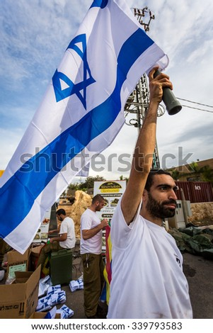 Mount Carmel, Israel - October 28, 2015: Israeli soldier with national flag. Group of them was installing Israeli flag before bicycle race. - stock photo