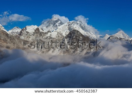 Mount Everest view from Gokyo Ri. Picturesque mountain valley filled with curly clouds at sunset. Everest dramatic snowy peak rise above river of clouds. Sagarmatha National Park, Nepal, Himalayas. - stock photo