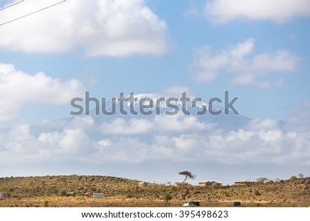 Mount Kilimanjaro, Tanzania., the highest mountain in Africa. Traditional african savannah village in foreground. - stock photo