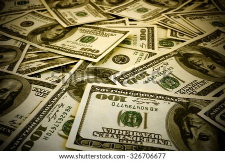 Mount of hundred dollar banknotes background texture warm filtered high contrasted with vignetting effect - stock photo
