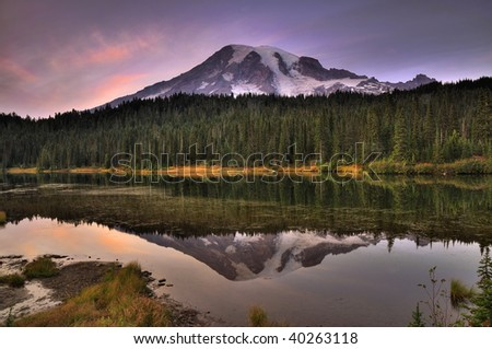 Mount Rainier reflected across the reflection lakes at dusk under a dramatic sky - stock photo