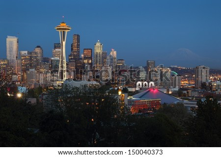 Mount Rainier, Seattle Twilight. Seattle, Washington skyline at twilight. The landmark Space Needle lit up as Mt. Rainier fades in the background. USA.  - stock photo