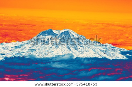 Mount Rainier with fresh snow and low clouds, aerial view, Washington - stock photo