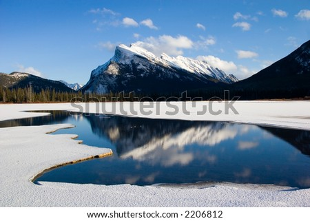 Mount Rundle reflected in the ice-covered Vermillion Lakes - stock photo