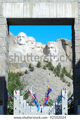 Mount Rushmore and alley of state flags through a stone doorway - stock photo