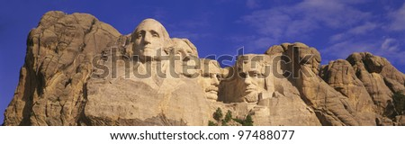 Mount Rushmore National Monument against a blue sky. Faces of George Washington, Thomas Jefferson, Theodore Roosevelt, and Abraham Lincoln. - stock photo