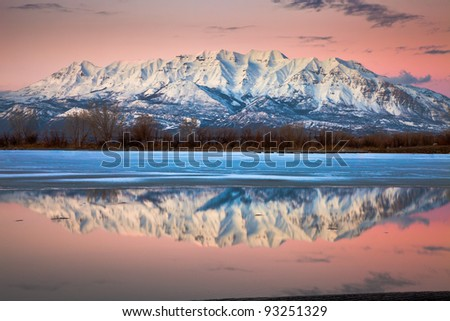 Mount Timpanogos at Dusk Reflecting off Icy Lake - stock photo