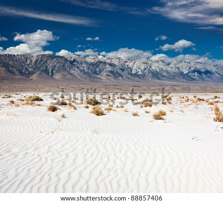 Mount Whitney and the Sierra Nevada rising above the Mojave Desert sands - stock photo
