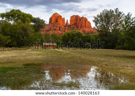 Mountain and old historical house reflected in the puddle - stock photo