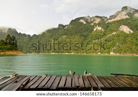 Mountain and river front of the hut while it was raining in Ratchaprapha Dam at Khao Sok National Park, Surat Thani Province, Thailand  - stock photo