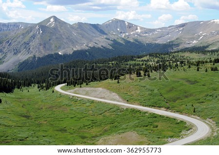 Mountain and Road - Part of Cottonwood Pass, a scenic back-country road, near its summit (12,126 feet) in Colorado. It is usually closed from early November to late May each year due to heavy snowfall - stock photo