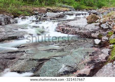 Mountain beautiful waterfall cascades with flowing clear water from the tops - stock photo