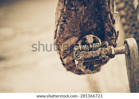 mountain bike clipless shoes with mud and dirt stuck in the pedal  - stock photo