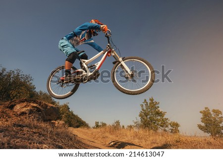 Mountain Bike cyclist jumping. Downhill biking. Extreme sports cycling. - stock photo