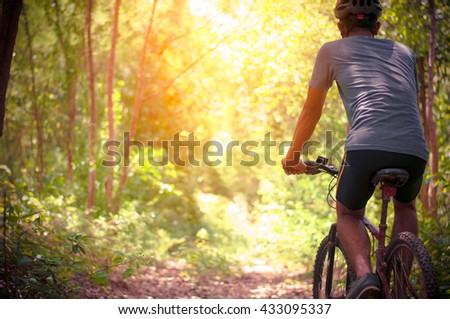 Mountain Bike cyclist riding single track at sunrise healthy lif - stock photo