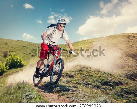 Mountain bike. Cyclist riding the bicycle down on mountain trail. Downhill. - stock photo